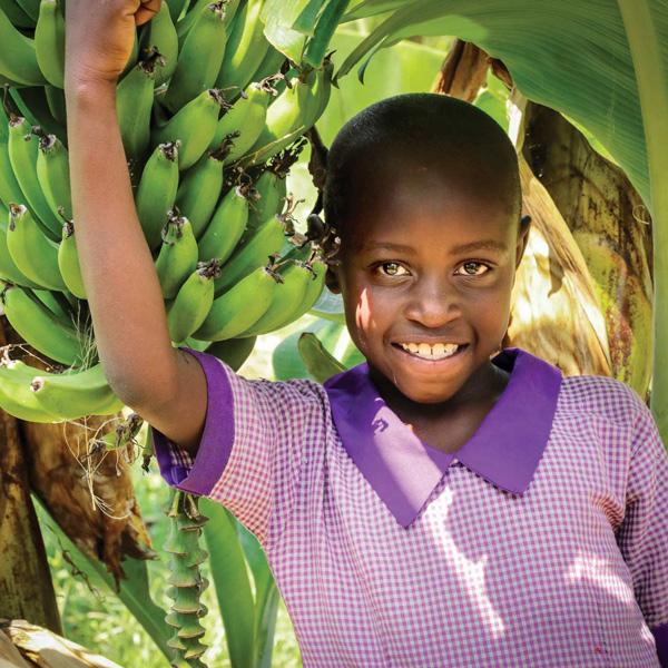Child next to banana tree.