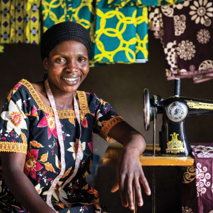 Woman smiling near sewing machine.