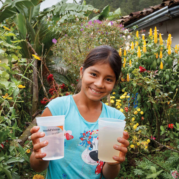 Girl holding a glass of clean water and a glass of dirty water.