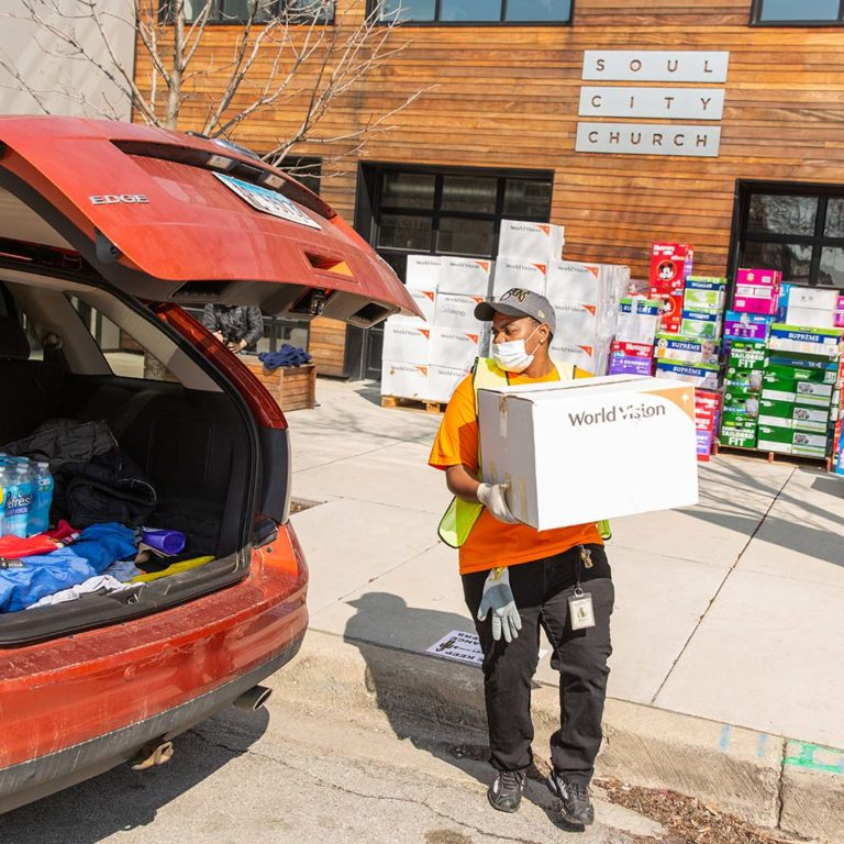 World Vision employee loading donation item for families